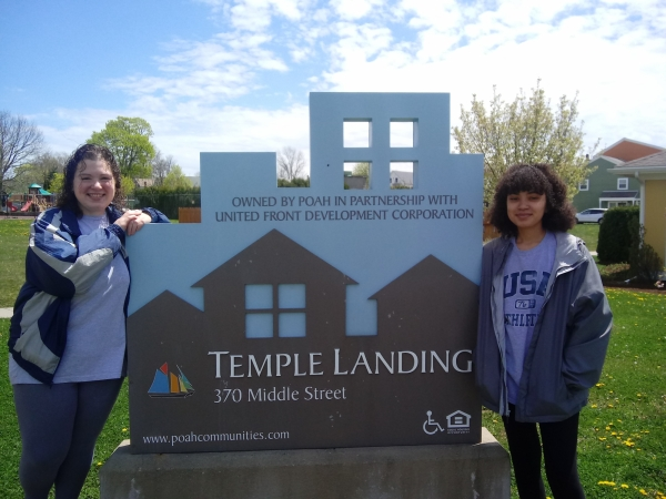 Fraces & Ryjani standing at temple landing sign
